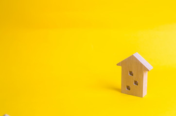 Wooden figure of a multi-storey house on a yellow background. Three-story house. Buying and selling of real estate, construction. Apartments and apartments. Minimalism. for presentations.