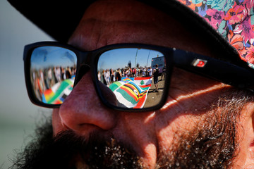 The UNESCO world heritage Cologne Cathedral and various flags are reflected in the glasses of a reveller during the annual Christopher Street Day gay pride parade in Cologne