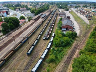 Cargo and passenger wagons on train station in city, aerial view.