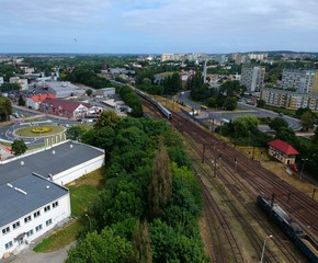 Fotobehang Treinstation Cargo and passenger wagons on train station in city, aerial view, road roundabout intersection with bridge