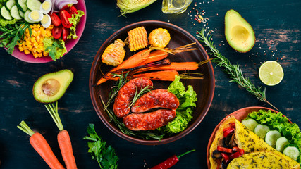 Grilled sausage. Baked Corn and Carrots. On a wooden background. Top view. Copy space.