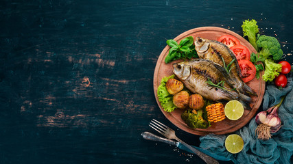Baked fish with spices and vegetables. Carp On a wooden background. Top view. Copy space.