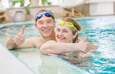 happy elderly couple in the pool showing thumbs up