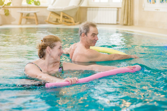 senior woman and man doing aqua fitness with swim noodles