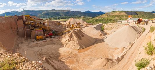 Vista panoramica de gravera con cintas de distribucion de la grava segun tamaños , molinos de machacar piedras y montones de arena y grava en cantera al aire libre