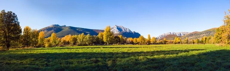 Vista panoramica de Paisaje  otoñal de prados verdes arboledas y montañas rocosas  al fondo. Con pequeño pueblo escondido entre los arboles