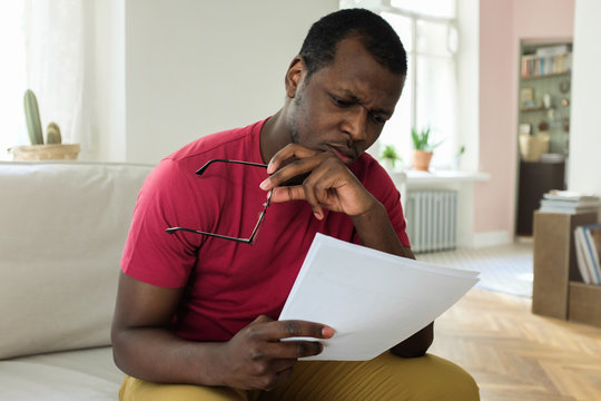 Photo of young African American man sitting on couch at home holding documents or bills, having taken off glasses, looking deeply troubled because of high expenses and facing problems with budget