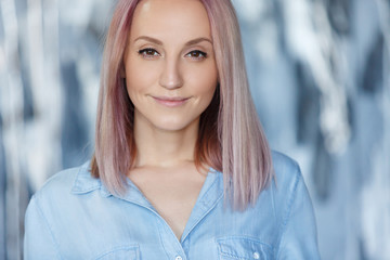 Closeup portrait of joyfull nice-looking female with pleasand smile and pink hair kindly looks at the camera. Lovely young girl models in blue denim shirt has good mood. People, lifestyle