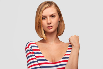 Studio shot of serious beautiful female with freckled skin, looks mysteriosly and thoughtfully, wears striped casual jacket, isolated over white background. Confident Caucasian woman indoor.