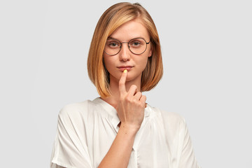 Indoor shot of serious self assured female contemplates about future plans, wants to change job position, dressed in casual oversized white shirt, keeps fore finger on lips. stands in studio