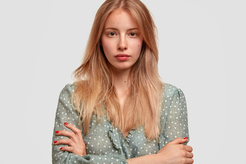 Headshot of pretty young female with appealing appearance, keeps arms folded, dressed in fashionable blouse, looks directly at camera, isolated over white background. People and beauty concept
