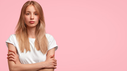 Attractive lovely young female with light hair, crosses hands, looks seriously at camera, contemplates about something, poses against pink background with copy space for your promotional text