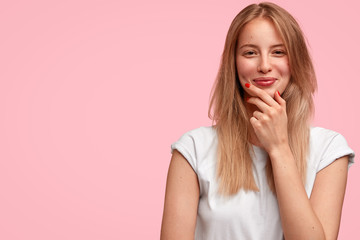 Wall Mural - Isolated shot of happy European female holds chin, looks positively, hears pleasant strory from friend, dressed in casual outfit, has healthy skin, stands against pink background with copy space