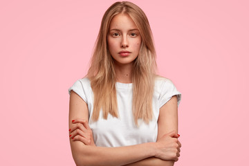 Confident attractive young European female keeps hands crossed, looks seriously directly at camera, contemplates about future plans after graduation university, isolated over pink background