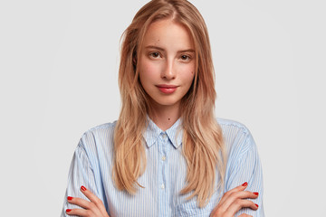 Horizontal shot of adorable young female with crossed hands, looks seriously at camera, has confident expression, isolated over white background. Attractive European woman in fashionable clothes