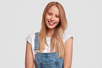 Wall Mural - Glad European young female with satisfied expression, smiles broadly, has healthy pure skin, dressed in denim stylish overalls, being in god mood after walk in park, isolated over white background