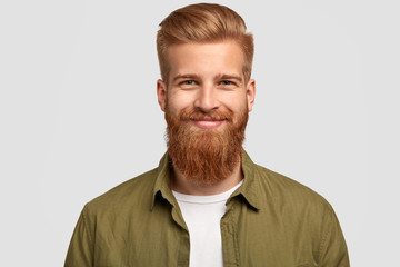 Joyful bearded male in good mood, rejoices successful day at university, has pleased expression, looks directly at camera, isolated over white background. People, happiness, emotions concept