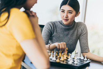 hand of asian woman friend moving chess figure in competition success play party games . strategy, management or leadership concept