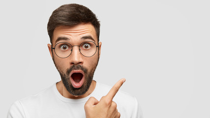 Close up shot of emotive shocked bearded young male opens mouth widely, stare at camera, points upwards aside at blank space, says: Wow, it`s something unbelievable! People and emotions concept Wall mural