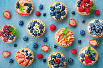 Wall Murals Dessert Colorful berry tartlets or cake for kitchen pattern. Pastry dessert from above.