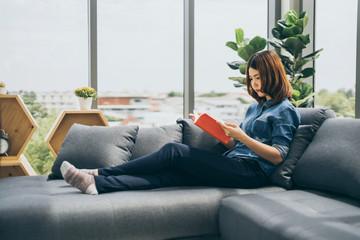 beautiful asian woman enjoy reading book hobby on sofa window background
