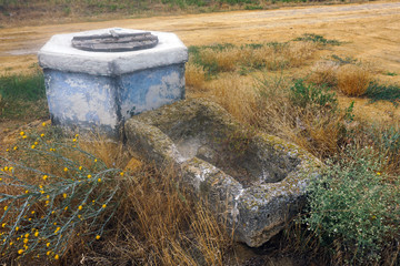 abandoned ancient trough for cattle near a closed well of stone