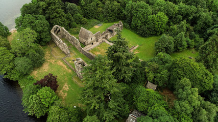 Aerial image of the ruins of Inchmahome Priory on a tree covered island on the picturesque Lake of Menteith.
