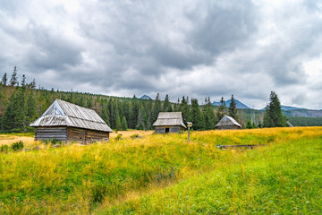 Wooden huts on a meadow in the Tatra Mountains in Poland with a dramatic cloudy sky