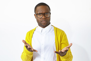 What are you waiting for. Horizontal shot of frowning indignant young Afro American male in stylish eyewear gesturing emotionally, expressing indignation, having puzzled look, being at loss