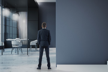 businessman in office with blank wall