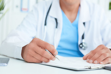 Closeup of male doctor's hands taking notes or fills in the client's medical card or prescribes medication. Ward round, patient visit check, medical calculation and statistics concept.