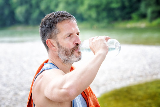 athlete standing outdoors and drinking from bottle