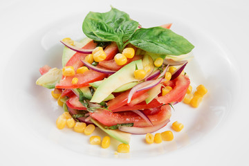 Vegetable salad with avocado, tomatoes and corn on white plate. Close-up