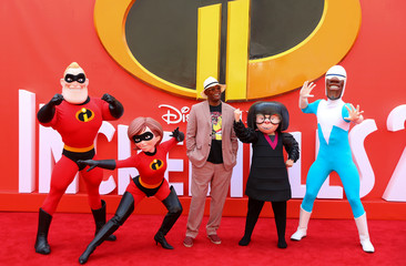 Actor Samuel L Jackson poses for photographs with characters from the flm as he arrives at the UK premiere of Incredibles 2 in London