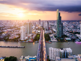 Fototapete - Aerial view of Bangkok skyline and skyscraper with light trails on Sathorn Road center of business in Bangkok downtown. Panorama of Taksin Bridge over Chao Phraya River Bangkok Thailand at sunset.