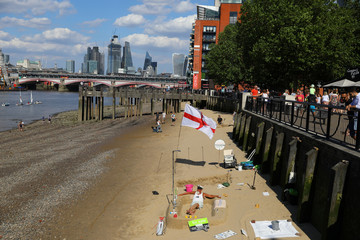A man sits on the sand of a beach revealed by a low tide of the River Thames, next to the South Bank in central London