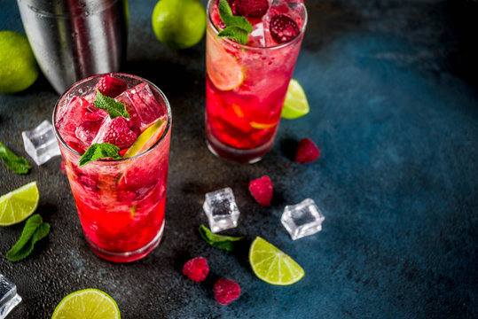 Iced summer drink cocktail, Raspberry and lime lemonade with fresh mint and lime, dark blue rusty background copy space