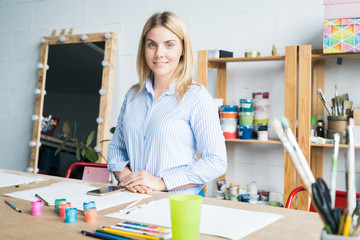 Waist up portrait of beautiful female artist looking at camera and smiling standing at table with paints and paintbrushes in workshop, copy space