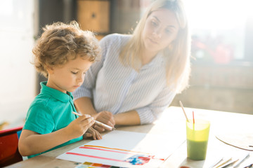Side view portrait of cute blond little boy paining pictures in sunlight sitting at table  with young mother or teacher, copy space