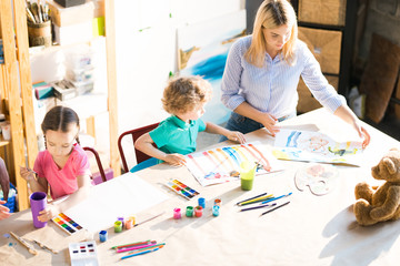 High angle portrait of young woman drawing with three little children sitting at wooden table in modern art studio for kids