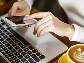 woman using cellphone and laptop while drinking coffee