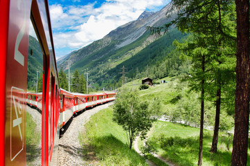 Running train at the railroad in Swiss mountains