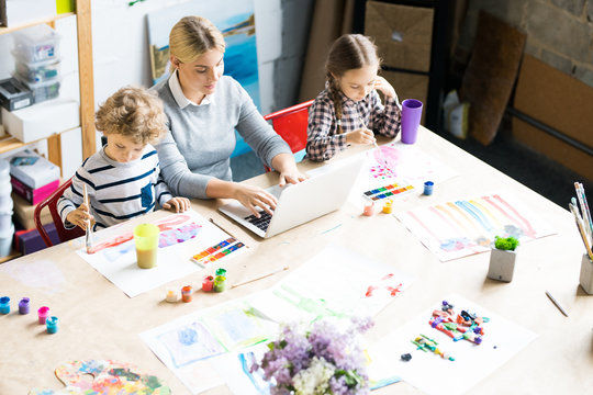 High angle portrait of young woman working at laptop with two kids painting beside her at table in modern apartment, copy space