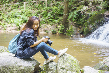 Photography and traveling Girls carrying cameras are on the waterfront in the jungle.