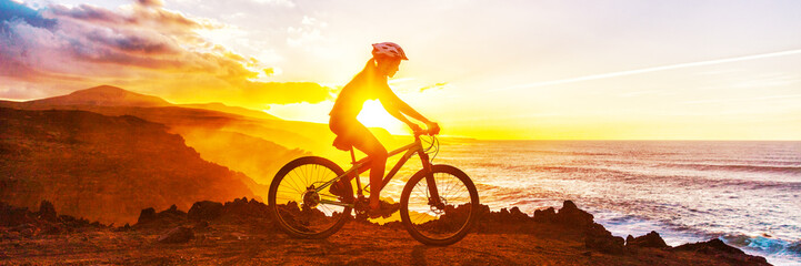 Mountain biking cyclist riding bike on coast trail against sunset. Silhouetter of woman doing sports outdoors banner panorama. Active lifestyle. Wall mural