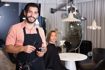 smiling man hairdresser and woman in salon