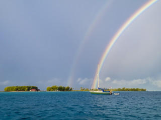 sailing yacht anchoring under a rainbow in the shallow, turquoise lagoon of the Makemo Atoll, Tuamotus, French Polynesia