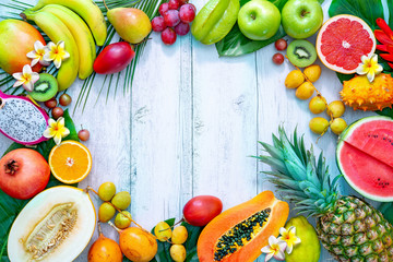 Assortment of tropical fruits with palm leaves and exotic flowers
