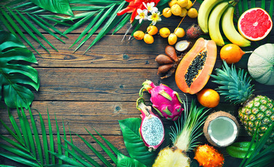 Poster de jardin Fruits Assortment of tropical fruits with leaves of palm trees and exotic plants on dark wooden background