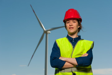 Portrait of a handsome successful young woman the chief designer in a green waistcoat and a red helmet against the background of windmills and a blue sky.